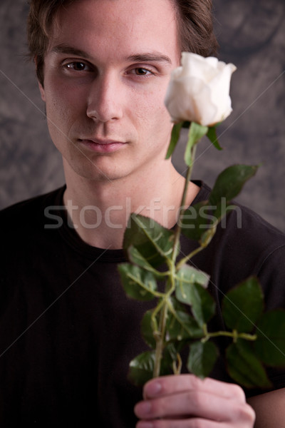 Stock photo: young fascinating man with a white rose