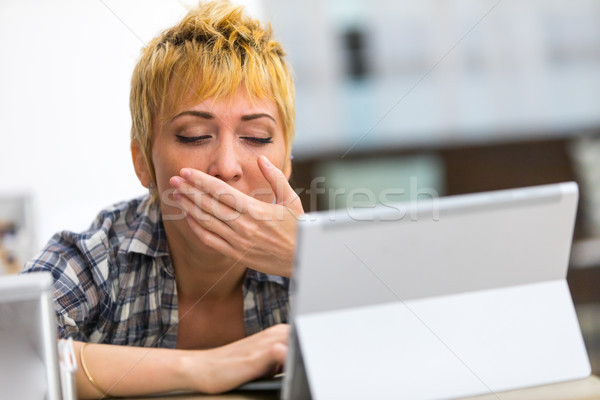 Stock photo: Bored young woman yawning as she works on a tablet