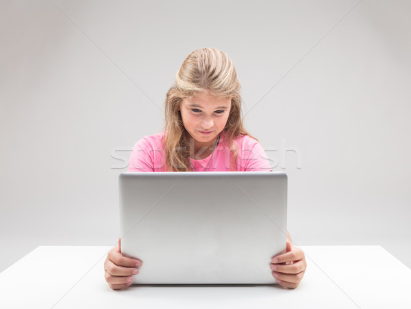 Stock photo: little girl being disgusted at her computer