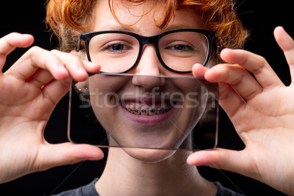 smile of a girl in braces through a transparent mobile phone Stock photo © Giulio_Fornasar