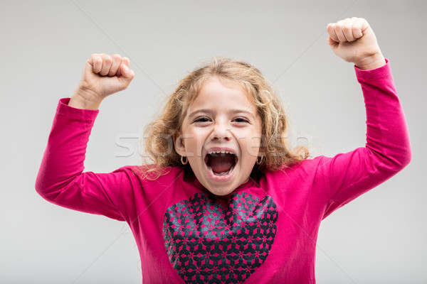 Laughing young schoolgirl raising hands Stock photo © Giulio_Fornasar