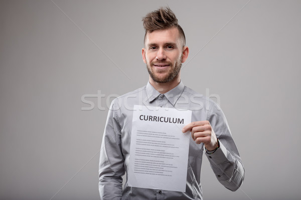 Trendy modern bearded young man holding up a typed Curriculum Stock photo © Giulio_Fornasar