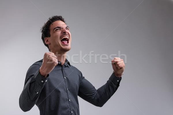 Fiatal férfi ujjongás fiatalember emelkedő karok Stock fotó © Giulio_Fornasar