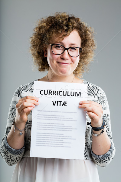 curly woman showing her resume on a gray background Stock photo © Giulio_Fornasar
