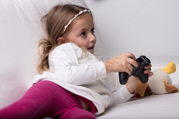 Little girl playing with a video game controller Stock photo © Giulio_Fornasar