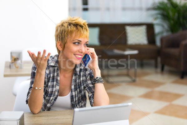 Pleased young woman chatting on her smartphone Stock photo © Giulio_Fornasar