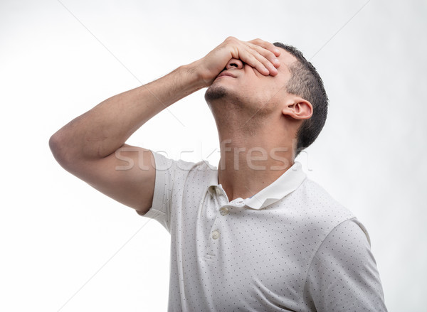 Man covering his face with his hand on white Stock photo © Giulio_Fornasar