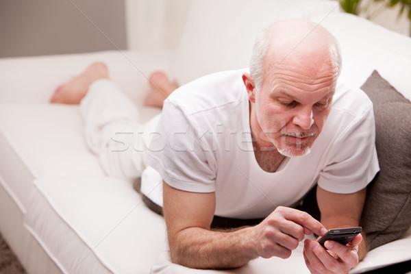 man using a smartphone on a sofa Stock photo © Giulio_Fornasar