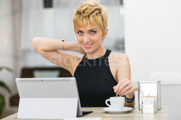 woman blending her coffee while using a computer in a bar Stock photo © Giulio_Fornasar