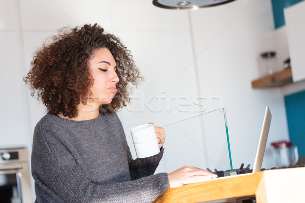 Disgruntled young woman pouting at her laptop Stock photo © Giulio_Fornasar