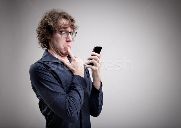 Człowiek telefonu komórkowego wątpliwy patrząc smartphone Zdjęcia stock © Giulio_Fornasar
