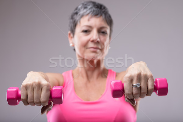 Older woman working out with a pair of dumbbells Stock photo © Giulio_Fornasar