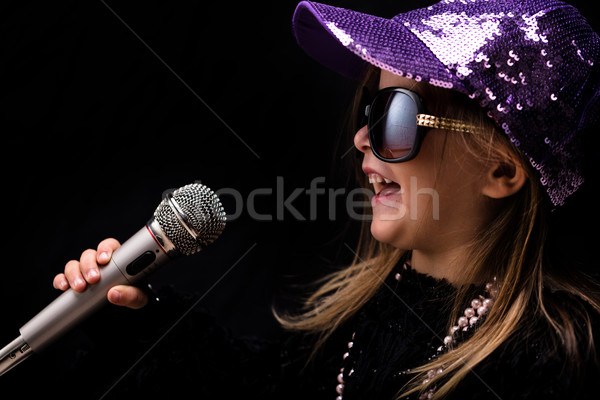 Charismatic trendy little girl singing into a mike Stock photo © Giulio_Fornasar