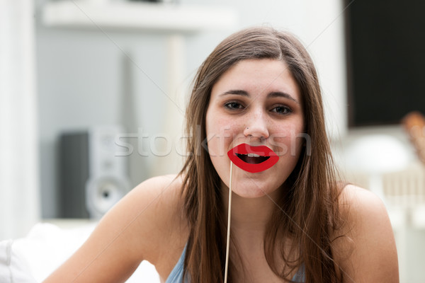 Playful woman holding lips prop near mouth Stock photo © Giulio_Fornasar