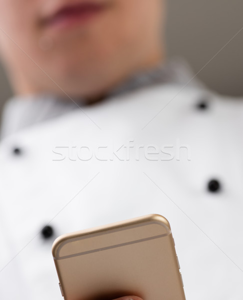 young chef ordering online with his smartphone Stock photo © Giulio_Fornasar