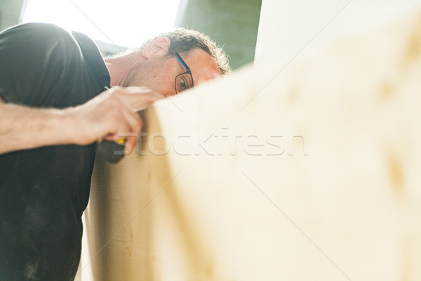 Stock photo: woodworker artisan in his workshop measuring