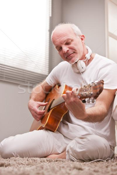 Homem maduro jogar guitarra casa tapete sala de estar Foto stock © Giulio_Fornasar