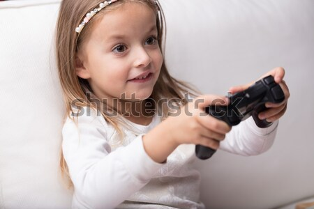 Cute playful little girl with a game controller Stock photo © Giulio_Fornasar