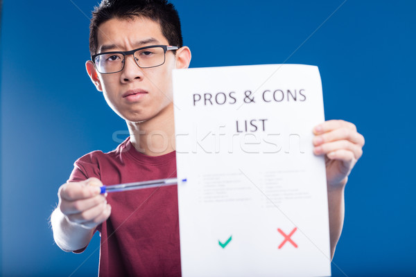 worried asian guy showing a pros and cons list Stock photo © Giulio_Fornasar
