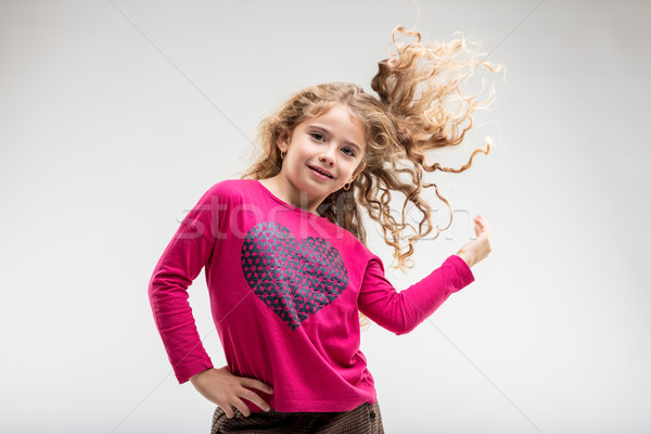 Cheerful preteen girl playing with her curly hair Stock photo © Giulio_Fornasar