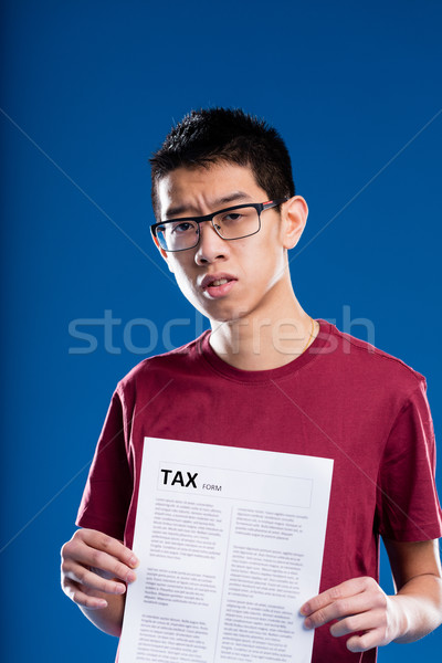 doubtful asian man holding a tax form Stock photo © Giulio_Fornasar