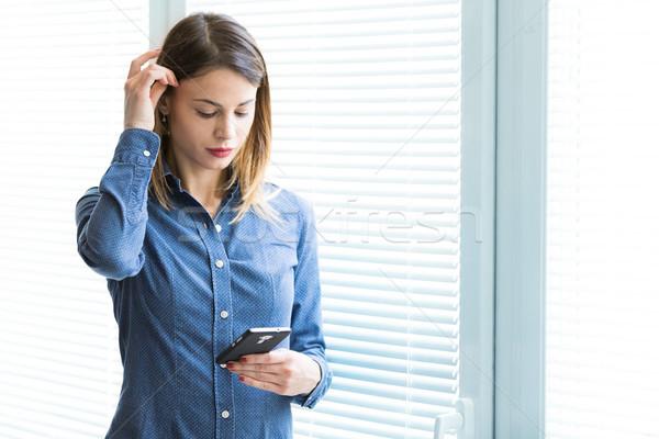 Serious young woman reading a text message Stock photo © Giulio_Fornasar