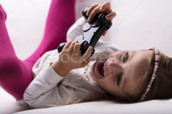 little girl playing videogames at home Stock photo © Giulio_Fornasar
