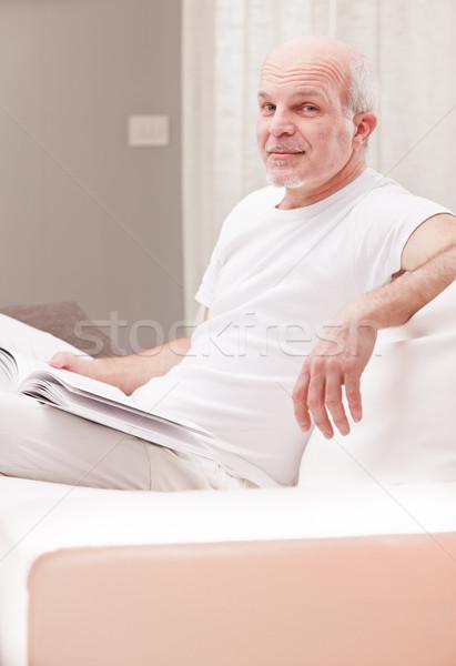 Sinsi gülümseme adam okuma kitap oturma odası Stok fotoğraf © Giulio_Fornasar