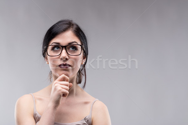Attractive woman in glasses deep in thought Stock photo © Giulio_Fornasar