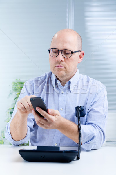 upright nerdy clerk with two telephones Stock photo © Giulio_Fornasar