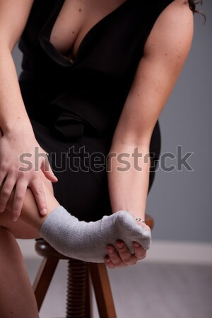 woman holding up her aching foot Stock photo © Giulio_Fornasar