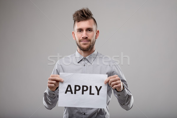 Young bearded man holding up a typed sign - Apply Stock photo © Giulio_Fornasar