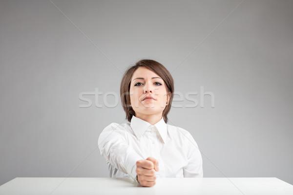 Határozott fiatal nő ököl asztal bámul kamera Stock fotó © Giulio_Fornasar