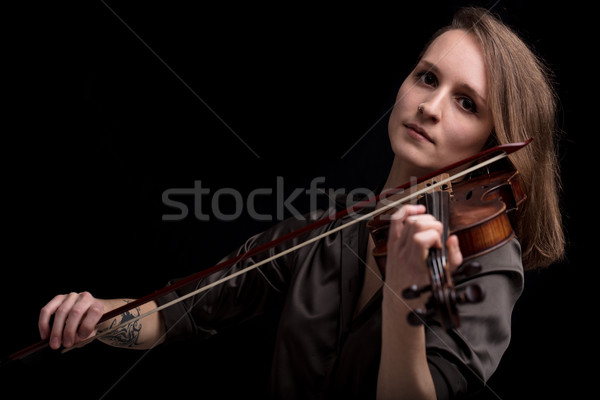 Stock photo: tattooed violinist woman playing in black background