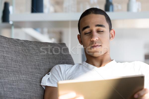 Uomo divano guardando tablet fronte view Foto d'archivio © Giulio_Fornasar