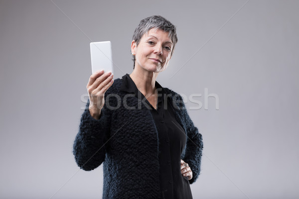 Attractive self-assured woman holding a mobile Stock photo © Giulio_Fornasar