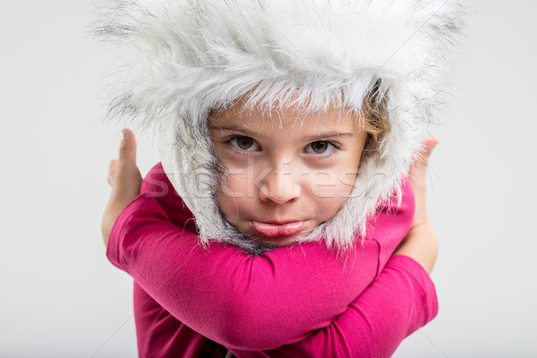 Stock photo: Young schoolgirl wearing fluffy cap making face