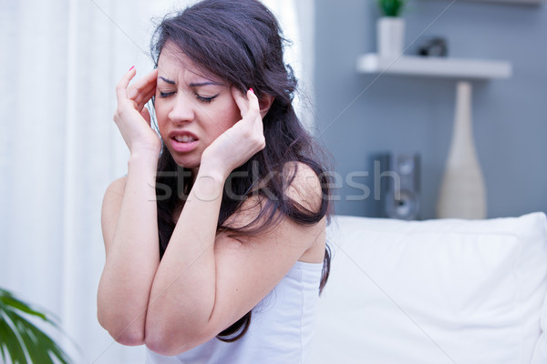 girl with painful headache in her living room Stock photo © Giulio_Fornasar