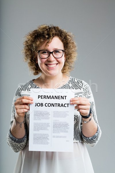 curly smiling woman holding a premanent job contract Stock photo © Giulio_Fornasar