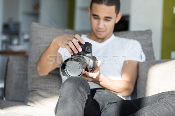 Man looking at DSLR camera while sitting indoors Stock photo © Giulio_Fornasar