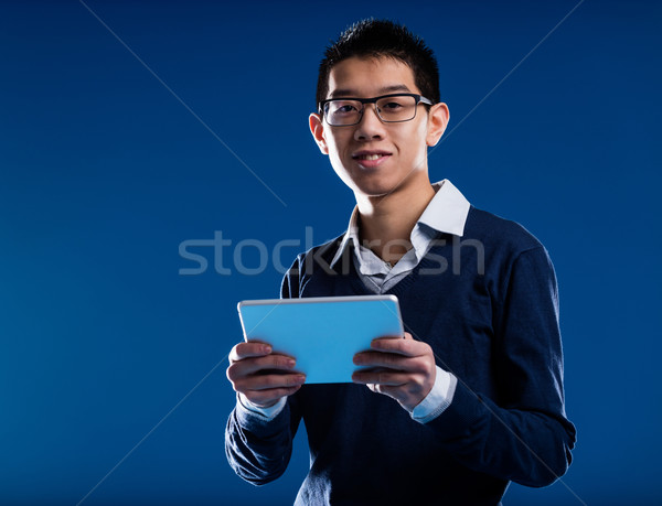 chinese guy smiling holding an ipad Stock photo © Giulio_Fornasar