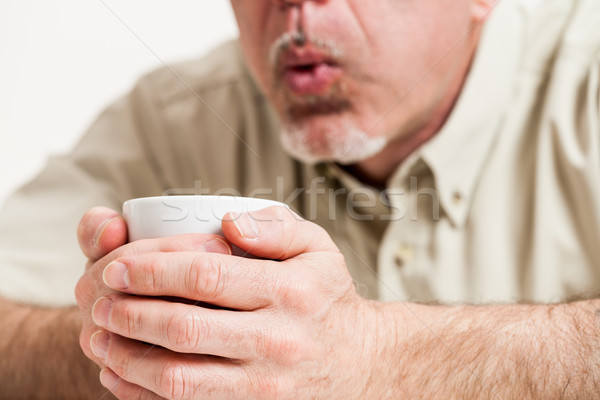 Cropped head and shoulders of man blowing into cup Stock photo © Giulio_Fornasar
