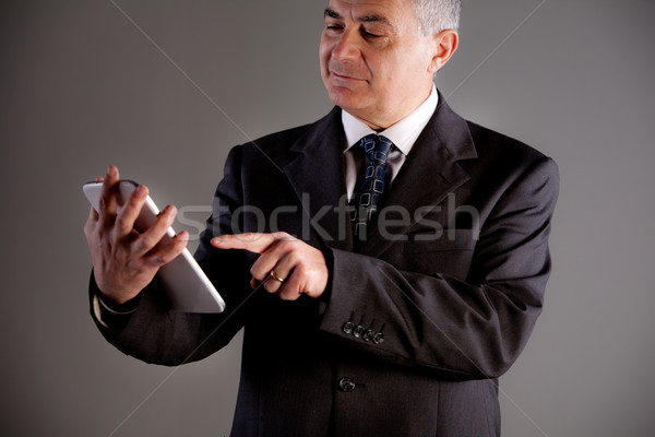 Stock photo: Senoir man using successfully a tablet