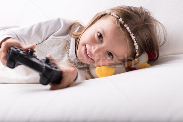 Gülen güzel küçük kız oynama video oyunları peluş Stok fotoğraf © Giulio_Fornasar