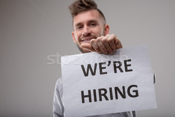 Smiling man holding up a sign We're Hiring Stock photo © Giulio_Fornasar