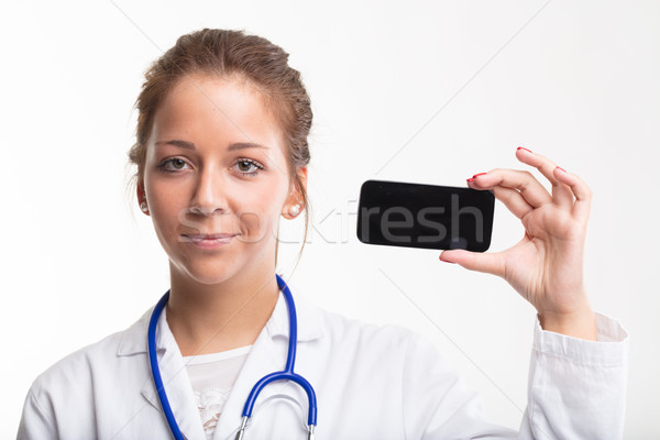 Smiling young nurse holding a mobile phone Stock photo © Giulio_Fornasar