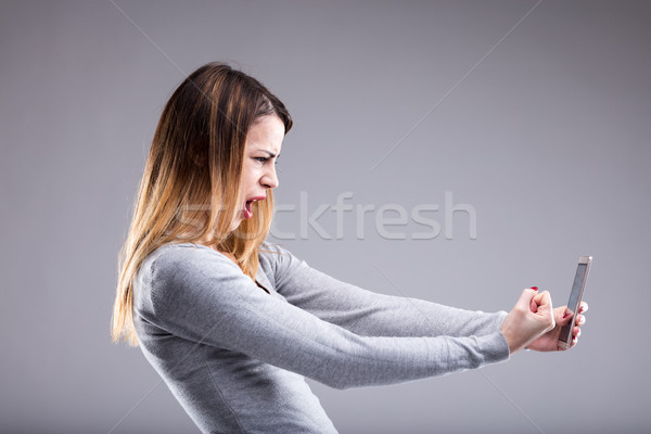 angry woman against her phone Stock photo © Giulio_Fornasar
