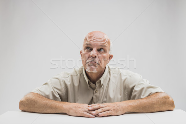 Thoughtful older balding man sitting at a table Stock photo © Giulio_Fornasar