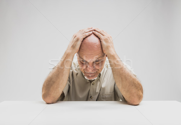 Depressed man sitting at table Stock photo © Giulio_Fornasar
