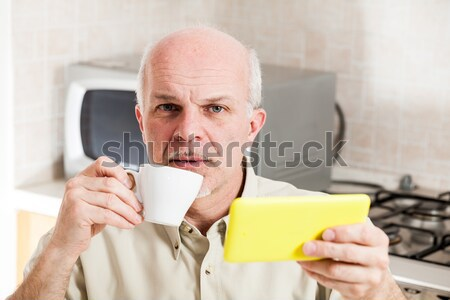 Grinning man holding digital reader and cup Stock photo © Giulio_Fornasar